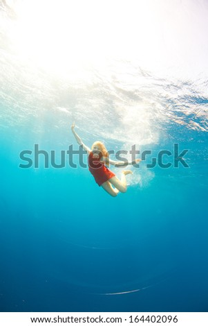beautiful girl diving under the sea - stock photo