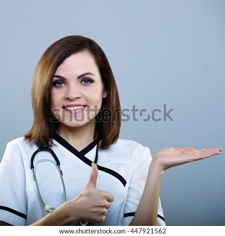 beautiful girl doctor holding on one hand an imaginary thing, and the other shows thumb