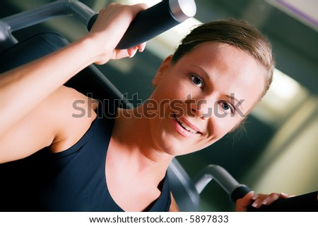 Beautiful girl doing fitness exercises in a gym - stock photo