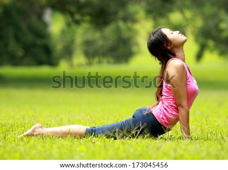 beautiful girl doing workout on grass in the morning - stock photo