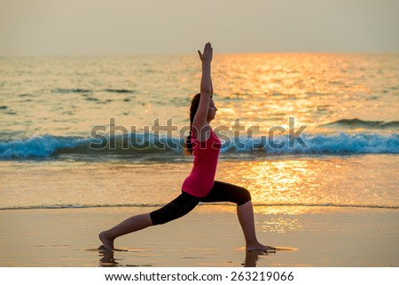 beautiful girl doing yoga near the ocean barefoot
