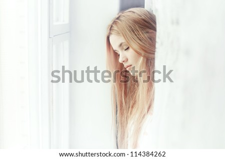 beautiful girl dreams of the window - stock photo
