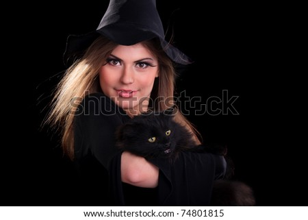 Beautiful girl dressed as a witch holding cat