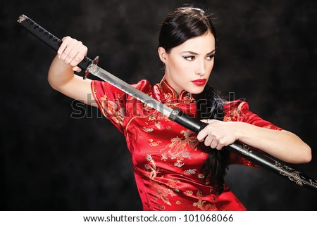 beautiful girl dressed in a kimono with katana in her hands - stock photo
