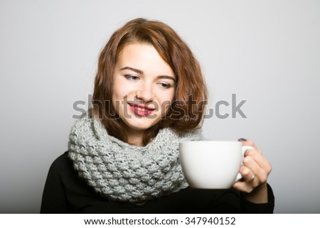 beautiful girl drinking coffee or tea to keep warm in the winter, the office manager concept shot isolated on gray background