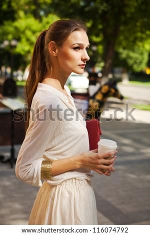 beautiful girl drinking coffee, walking around town - stock photo