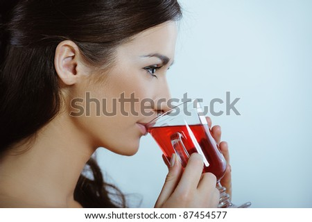 Beautiful girl drinking healthy hot red tea - stock photo