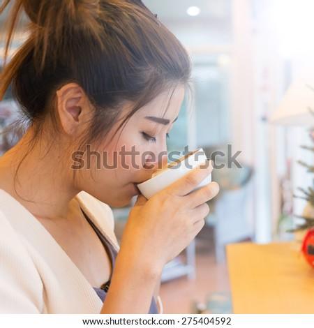 beautiful girl drinking hot coffee or tea in coffee cafe, model asia women, female of thai people - stock photo