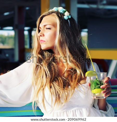 Beautiful girl drinking mojito cocktail. Photo toned style Instagram filters