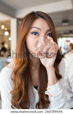 Beautiful girl drinking pure water in the cafe - stock photo