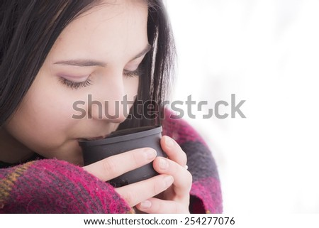 Beautiful Girl Drinking Tea or Coffee. Beauty Woman enjoying Coffee. Cup of Hot Beverage.Beautiful young brunette woman with a hat - stock photo