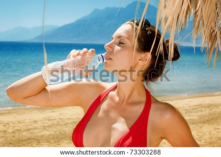 Beautiful girl drinking water against blue sea - stock photo
