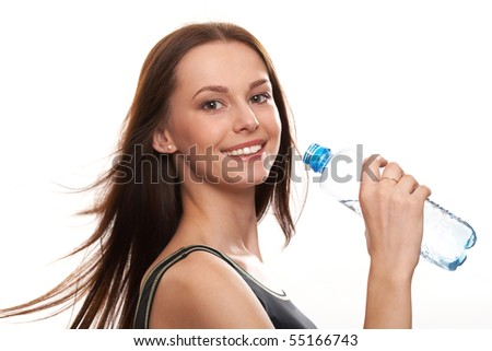Beautiful girl drinking water from blue bottle on blue background - stock photo