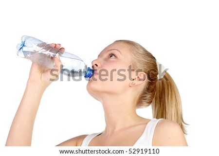 beautiful girl drinks mineral water from plastic bottle. The concept of healthy way of life.
