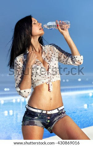 beautiful girl drinks water from bottle, thirst in hot day - stock photo