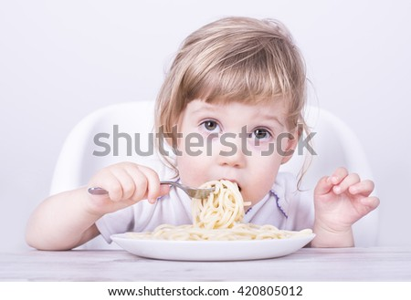 Beautiful girl eating and playing with spaghetti and fork.