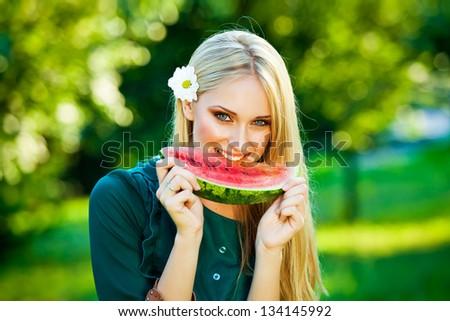 Beautiful girl eating fresh watermelon - stock photo