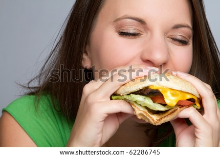 Beautiful girl eating hamburger food - stock photo