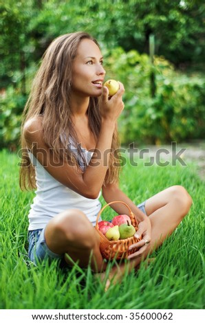 Beautiful girl eating pear on the green grass - stock photo