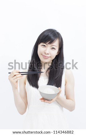 Beautiful girl eating rice with chopsticks, isolated on white background - stock photo