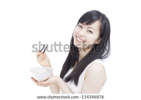 Beautiful girl eating rice with sticks, isolated on white background - stock photo