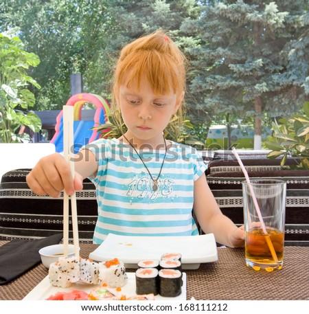 Beautiful girl eats sushi - stock photo