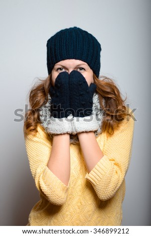 beautiful girl embarrassed, bright in yellow, lifestyle winter clothes studio photo isolated on a gray background