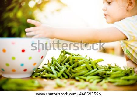 Beautiful girl enjoying outside and peeling peas off. - stock photo