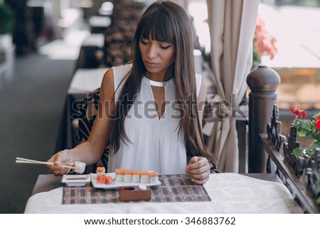 beautiful girl enjoying sushi in a cafe on a sunny day - stock photo