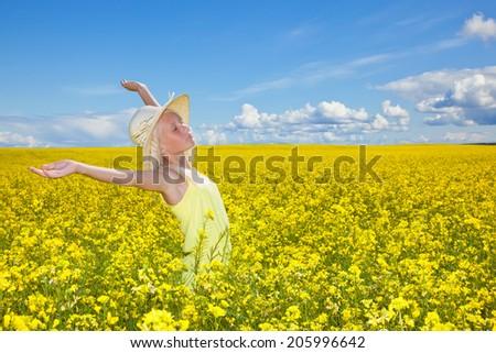 Beautiful girl enjoying the summer sun in the field. - stock photo