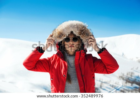 beautiful girl enjoying the sun, winter day in the mountains - stock photo