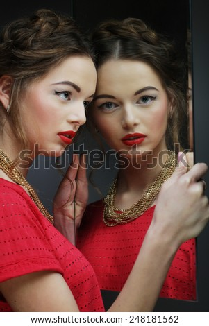 beautiful  girl female model with bright makeup  and her reflection in mirror table