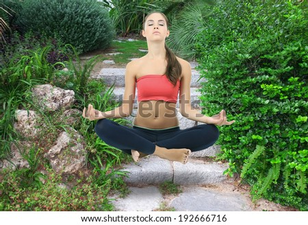 Beautiful girl fly and meditating in yoga pose - stock photo