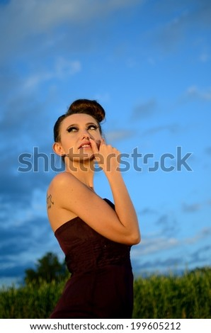 Beautiful girl from Poland, outdoor portrait. Young female model posing with different hands gesture. Blue sky with single clouds and green fields as background.