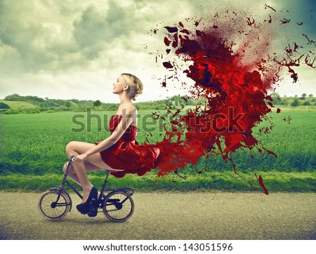 beautiful girl goes by bicycle with red dress - stock photo