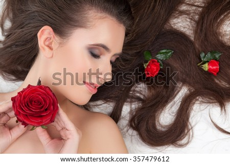 Beautiful girl has red roses in her long hair. She is lying and smiling. The lady is holding a flower under her naked body. Her eyes are closed with enjoyment - stock photo
