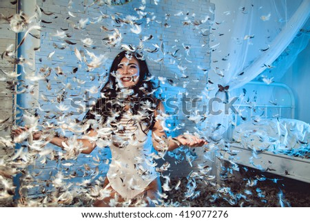 Beautiful girl having a lot of fun in feathers room - stock photo