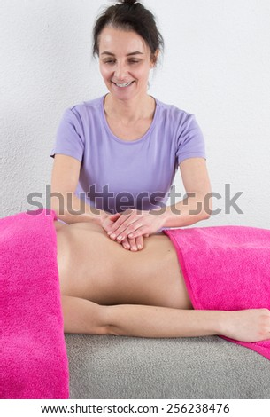 Beautiful girl having stomach massage, ayurveda massage - stock photo