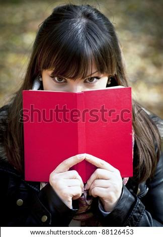 Beautiful girl hiding behind the book - stock photo