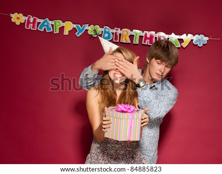 Beautiful girl hold gift with friend at birthday party - stock photo