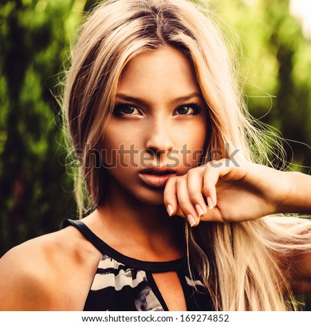 Beautiful girl holding a hand to his face, close-up portrait - stock photo