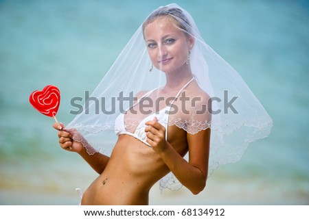 Beautiful girl holding a lollipop on the beach - stock photo