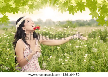 Beautiful girl holding a red flower in the park
