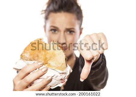 beautiful girl holding a sandwich and showing thumbs down - stock photo
