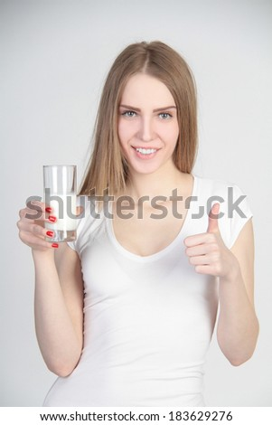 Beautiful girl holding glass of milk