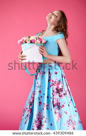 Beautiful girl holding large bouquet of paper flowers in box