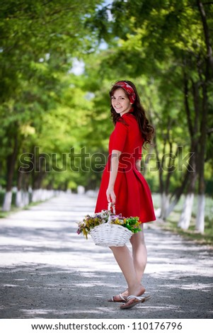 beautiful girl holding  on hands basket with garden flowers