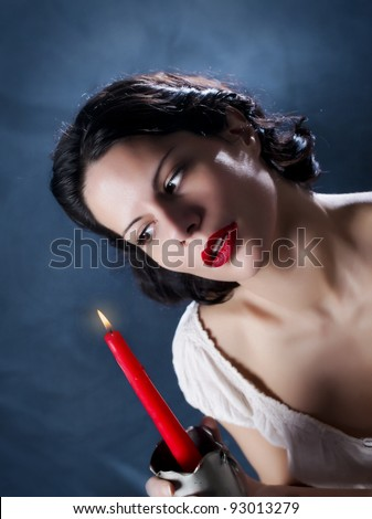 Beautiful girl holding red candle and look at the flame/Candle and Beauty - stock photo
