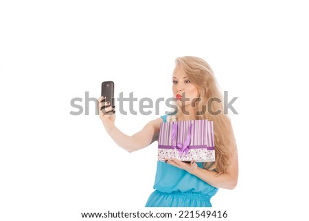 Beautiful girl holding shopping bags and taking selfie with cell phone isolated on white background