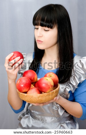 Beautiful girl holds in hands red apples on grey background